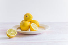 Heap of yellow lemons on a plate. Some sliced stock image