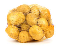 Heap of yellow raw potatos in red string bag Royalty Free Stock Photography
