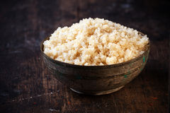 Heaped bowl of healthy cooked quinoa. Side angle view of a heaped rustic bowl of healthy cooked quinoa, a pseudo-cereal whose seeds are rich in protein and Stock Photos