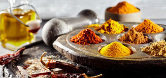 Heaped ground spices in an antique plate. With turmeric, curcuma, cayenne, chilli, cinnamon and curry alongside a decanter of olive oil and dried chili pods Royalty Free Stock Image