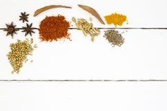 Heaped spices on white table. Heaped herbs and spices on white table closeup Royalty Free Stock Photo
