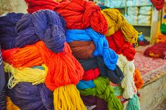 The colorful yarns in Vakil Bazaar, Shiraz, Iran. The heaps of colorful woolen and cotton skeins of yarn in warehouse-store of  Vakil Bazaar, Shiraz, Iran stock images