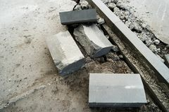 Heaps of curdstones lying on the sidewalk near the pit for installing a border. Broken asphalt surface on other side. Repair of ro. Heaps of curdstones lying on royalty free stock photography