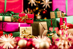 Heaps of Little Xmas Gifts Between Straw Stars. Plenty of small Christmas presents piled up before larger wrapped gifts in the rear. Narrow depth of field Royalty Free Stock Images