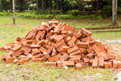 Heaps of red clay bricks at construction site. Heaps of red clay bricks unloaded at an open area of a construction site Royalty Free Stock Photo
