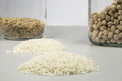 Heaps of rice grains in front of chickpeas and lentils Stock Images