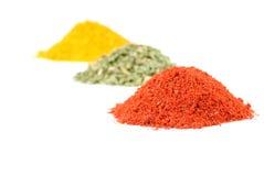 Heaps of various ground spices on white stock photos