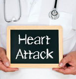 Heart Attack. Doctor or physician with stethoscope holding a blackboard with white chalk text reading  'heart attack Stock Photos