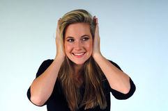 Hear no Evil. Woman with hands over her ears, smiling and looking to her left royalty free stock image