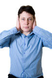 Hear no evil. Business man with blue shirt holding both hands on his ears to prevent him from hearing Stock Photos