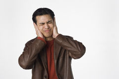 Hear no evil. Young Latino man covers his ears Royalty Free Stock Images