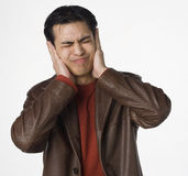 Hear no evil. Young Latino man covers his ears Stock Photography