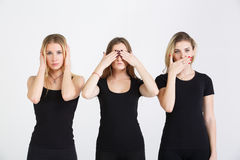 Hear no evil, see no evil, speak no evil. Three young women in black clothes isolated at white background showing blind, deaf and dumb: wise monkey scene - hear royalty free stock photos