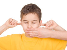 Hear see and speak no evil. A boy covering his ears in hear no evil royalty free stock photo