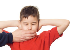 Hear see and speak no evil. A boy covering his ears in hear no evil royalty free stock photography