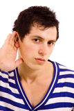 Hearing. Young man with open hand gesturing hearing something on white background stock image