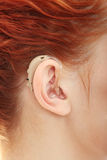 Hearing aid. Redhead woman wearing hearing aid Stock Image