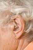 Hearing aid. Close-up of a seniors ear with a behind-the-ear-hearing device Stock Image