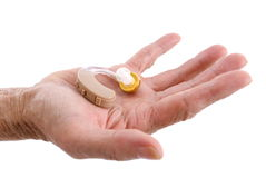Hearing aid. Hands showing a Hearing aid on white background Royalty Free Stock Images