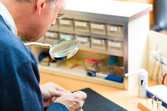Acoustician working on a hearing aid. Hearing aid acoustician at work, he is working on a hearing aid for hearing impaired persons stock photography