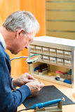 Acoustician working on a hearing aid Stock Images
