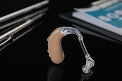 Hearing aid on black table. Medical device royalty free stock photo