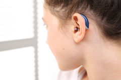 Hearing aid. Cheerful girl assumes hearing aid viewing in the mirror Royalty Free Stock Image