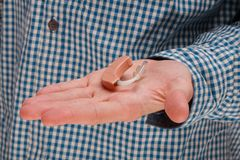 Hearing aid close-up with a guy with hearing problems stock image
