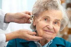 Hearing Aid. Doctor inserting hearing aid in senior's ear Stock Image