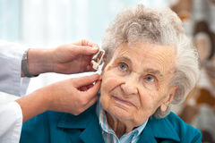 Hearing Aid. Doctor inserting hearing aid in senior's ear stock photo