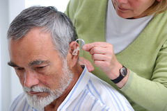 Hearing Aid. Doctor inserting hearing aid in senior's ear Royalty Free Stock Photo