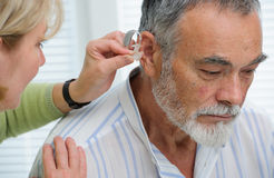 Hearing Aid. Doctor inserting hearing aid in senior's ear Royalty Free Stock Image