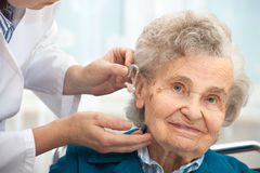 Hearing Aid. Doctor inserting hearing aid in seniors ear Royalty Free Stock Images