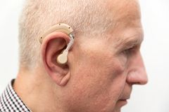 Hearing aid in the ear of aged old man royalty free stock photography