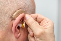 Hearing aid in the ear of aged old man royalty free stock image