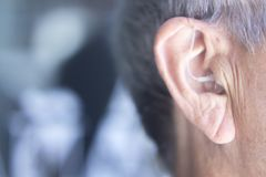 Hearing aid in ear. Modern digital in the ear hearing aid for deafness and the hard of hearing in aged man& x27;s ear stock photography