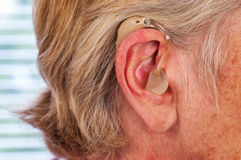 Hearing aid in the ear. Hearing aid on the women ear royalty free stock photography