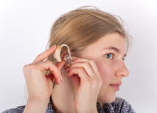 Hearing aid. Girl inserting her hearing aid Stock Photo