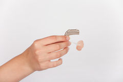 Hearing aid in a hand. Audiologists hand holds a hearing aid with earmold. Studio isolated stock photography