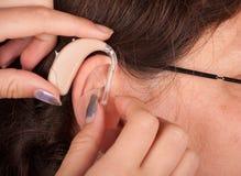 Hearing aid inserting Stock Photo