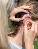 Hearing aid - inserting Royalty Free Stock Image