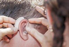 Hearing aid inserting Royalty Free Stock Photos
