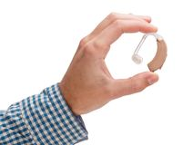 Hearing aid in a man`s hand. Isolated on white background. royalty free stock image