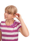 Hearing aid putting on. Young female putting on a hearing aid isolated on white Stock Images