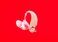 Hearing aid on red Stock Images