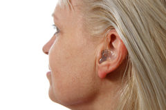 Hearing aid in woman`s ear Royalty Free Stock Images