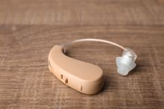 Hearing aid on wooden table, closeup. Medical device stock photo