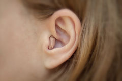 Hearing aid in your ear close-up. Modern equipment in medicine Royalty Free Stock Photography