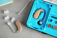Hearing aids and case on grey table. Top view royalty free stock photos