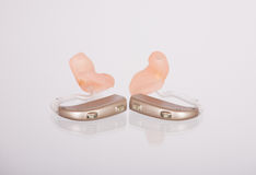 Hearing aids. Two hearing aids left and right with ear moulds on a mirroring glass surface Royalty Free Stock Photography